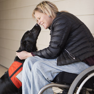 Woman with a disability smiling and touching noses with her service dog