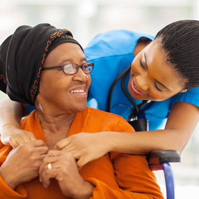 Young smiling female caregiver assisting smiling female senior